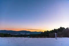 Prachtige de winterzonsondergang met bergmeningen en een toenemende maan met een poolster in de hoek en een voetbaldoel Rusland,  royalty-vrije stock afbeelding