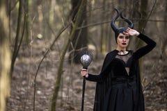Prachtige en Magische Maleficent Vrouw met Hoornen die in de Lente Leeg Bos met Oplichter stellen stock afbeelding
