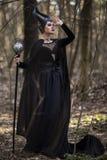 Prachtige en Magische Maleficent Vrouw met Hoornen die in de Lente Leeg Bos met Oplichter stellen stock afbeeldingen