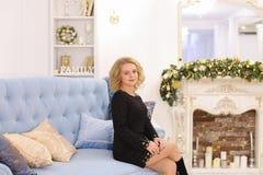 Prachtige jonge blonde vrouwen glimlachende en stellende zitting op laag Royalty-vrije Stock Foto's