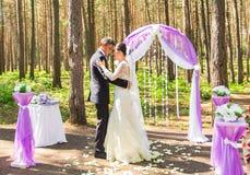 Prachtige modieuze rijke gelukkige bruid en bruidegom die bij een huwelijksceremonie in groene tuin dichtbij purpere boog met blo royalty-vrije stock afbeeldingen