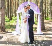 Prachtige modieuze rijke gelukkige bruid en bruidegom die zich bij een huwelijksceremonie in groene tuin dichtbij purpere boog be stock fotografie