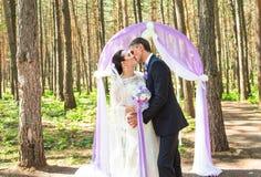 Prachtige modieuze rijke gelukkige bruid en bruidegom die zich bij een huwelijksceremonie in groene tuin dichtbij purpere boog be stock afbeelding