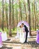 Prachtige modieuze rijke gelukkige bruid en bruidegom die zich bij een huwelijksceremonie in groene tuin dichtbij purpere boog be stock foto