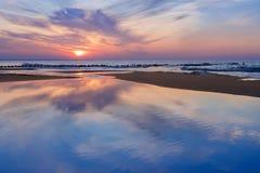 Prachtige overzeese zonsondergang met bezinning Stock Fotografie