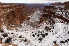 Prachtige Weg die onderaan Berghelling in Sneeuw winden Stock Afbeeldingen