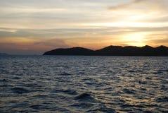 Prachtige zonsondergang over de bergen door het overzees stock foto
