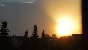 Prachtige zonsondergang over de stad De zon daalt en vormt een schitterende hemel Zonsondergang over de daken en de bomen stock videobeelden
