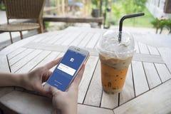 Prachuapkhirikhan,泰国威严6,2016 :拿着有Facebook页的妇女手一个智能手机在屏幕上,在咖啡咖啡馆 免版税库存图片