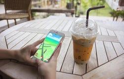 Prachuapkhirikhan, Thailand - August 6,2016: die Frauenhand, die intelligentes Telefon hält, um Pokemon zu spielen, gehen lizenzfreie stockfotografie
