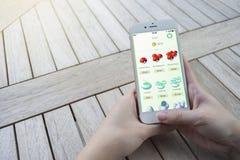 Prachuapkhirikhan Thailand - Augusti 6,2016: går den smarta telefonen för kvinnahandinnehavet som köper pokemonmynt i Pokemon, mo Arkivfoton