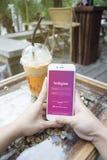 Prachuapkhirikhan, Thailand-herrliche 6,2016: Frauenhand, die Apple-iPhone mit Instagram-Anwendung auf dem Schirm, am Kaffeecafé  Lizenzfreie Stockbilder
