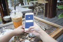 Prachuapkhirikhan, Thailand-herrliche 6,2016: Frauenhand, die einen Smartphone mit Facebook-Seite auf Schirm, am Kaffeecafé hält lizenzfreies stockfoto