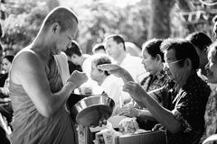 Prachuapkhirikhan, Thailand - November 16, 2015 : Unidentified man of Buddhist offer foods to a monk for make merit. In a Religious ceremony,black and white Stock Image
