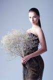 Pracowniana moda strzelająca: piękna młoda kobieta w smokingowym mienie bukiecie więdnący kwiaty Zdjęcia Royalty Free