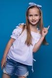 Pracowniany portret śliczna śmieszna mała dziewczynka na tle błękit ściana obraz stock