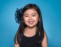 Pracowniany portret azjatykcia dziewczyna z szczęśliwym spojrzeniem przed błękitnym tłem fotografia royalty free