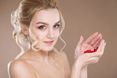 Pracowniany portret blondynka w ona ręk czerwone kapsuły witamina Zdjęcia Stock