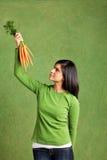 Pracowniany portret młoda kobieta trzyma up plika marchewki i patrzeje Fotografia Royalty Free