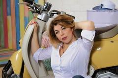 Pracowniany portret piękna kobieta w białej koszula z ręką w jej włosy pozuje z motocyklem zdjęcia royalty free