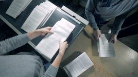 Pracownicy biorą drukującego papier od konwejeru i brogują je zbiory