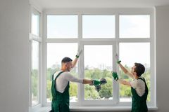 Pracownicy budowlani instalują okno fotografia stock