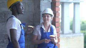 Pracownicy budowlani je gawędzić i kanapkę biorą przerwę zdjęcie wideo