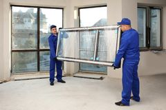 Pracownicy budowlani niesie nadokiennego szkło obrazy royalty free