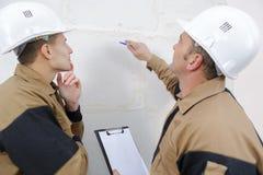 Pracownicy budowlani opowiada o ścianie obraz stock