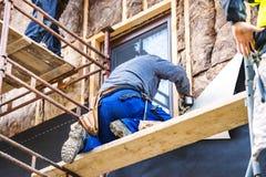 Pracownicy budowlani thermally izoluje domową fasadę z szklaną wełną zdjęcia royalty free