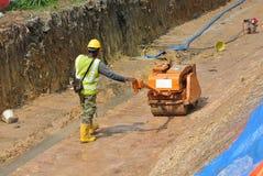 Pracownicy budowlani używa dziecko rolownika compactor Zdjęcie Royalty Free