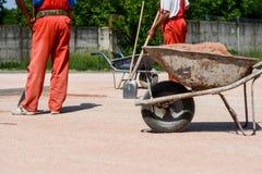 Pracownicy budowlani z łopatami Są ubranym czerwonych spodnia Obraz Stock