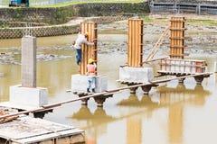 Pracownicy buduje bridżową podstawę przez jezioro Fotografia Stock