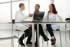 Pracownicy centrum medycznego obsiadanie przy jego biurkiem obraz stock