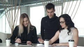 Pracownicy dyskutują przy biurkiem na którym kłama pastylka zbiory