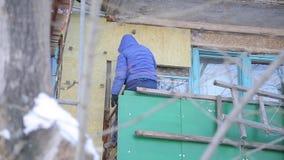 Pracownicy grżą fasadę budynek i naprawiają zbiory