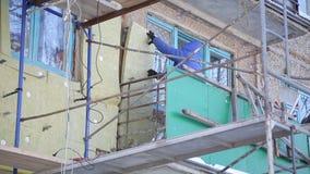 Pracownicy grżą fasadę budynek i naprawiają zbiory wideo