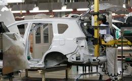 Pracownicy gromadzić samochód na linii montażowej w samochodowej fabryce zdjęcia stock
