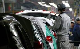 Pracownicy gromadzić samochód na linii montażowej w samochodowej fabryce obraz stock