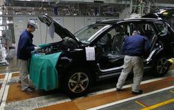 Pracownicy gromadzić samochód na linii montażowej w samochodowej fabryce fotografia royalty free