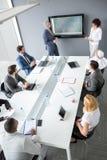 Pracownicy grupują przy spotkanie stołem słuchają kierownika Zdjęcia Stock