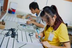 Pracownicy kleią magnesowego lampas na plastikowych kartach Zdjęcie Royalty Free