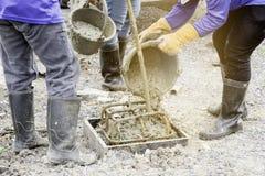Pracownicy nalewają beton z zbiornika robić palowemu kastingowi zdjęcia stock