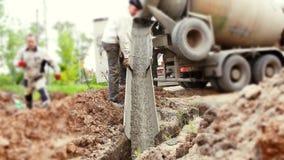 Pracownicy nalewają cementową podstawę z samochodem zbiory