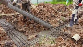 Pracownicy nalewający cementową podstawę buduje chałupę zbiory