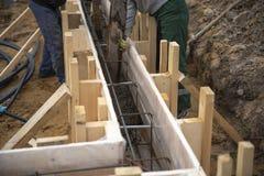 Pracownicy nalewaj? beton w podstaw? fotografia royalty free