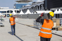 Pracownicy niosą budowa metalu drymby Zdjęcia Royalty Free
