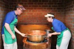 Pracownicy podnosi ampuła groszaka puszkują z rozciekłą czekoladą dla fudge, Pieprzowego pasa ruchu Fudge & cukierków, stosunek, P Obraz Stock