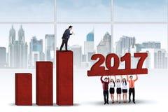 Pracownicy próbuje budować wykres z 2017 Obrazy Stock