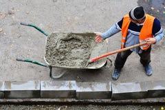 Pracownicy przeszuflowywają mokrego beton od wheelbarrow obrazy royalty free